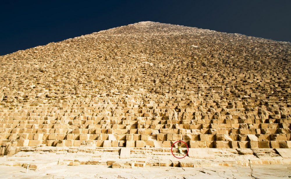 Una vista de las enormes piedras que forman el núcleo de la Gran Pirámide de Giza. Se da cuenta de la persona sentada en una de las piedras. Shutterstock